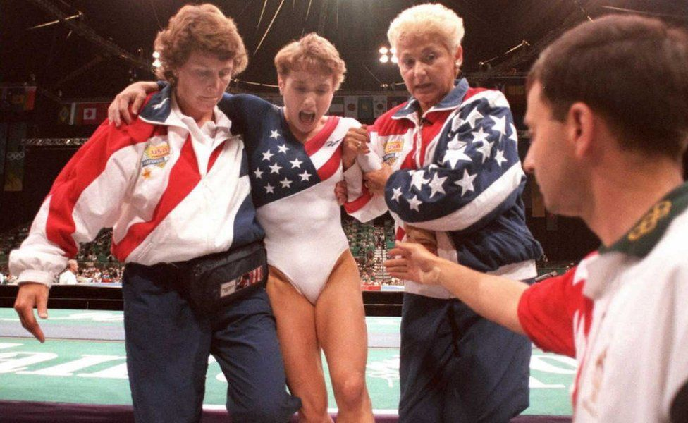 US gymnast Kerri Strug (2nd L) screams in pain as she is carried from the floor - 1996