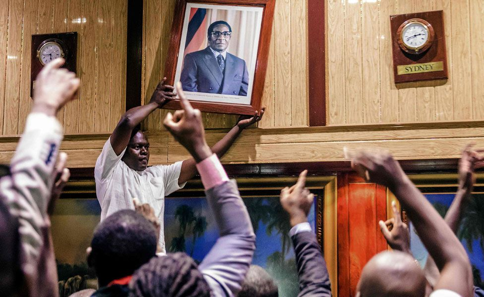 People remove, from the wall at the International Conference centre, where parliament had their sitting, the portrait of former Zimbabwean President Robert Mugabe after his resignation on November 21, 2017 in Harare.