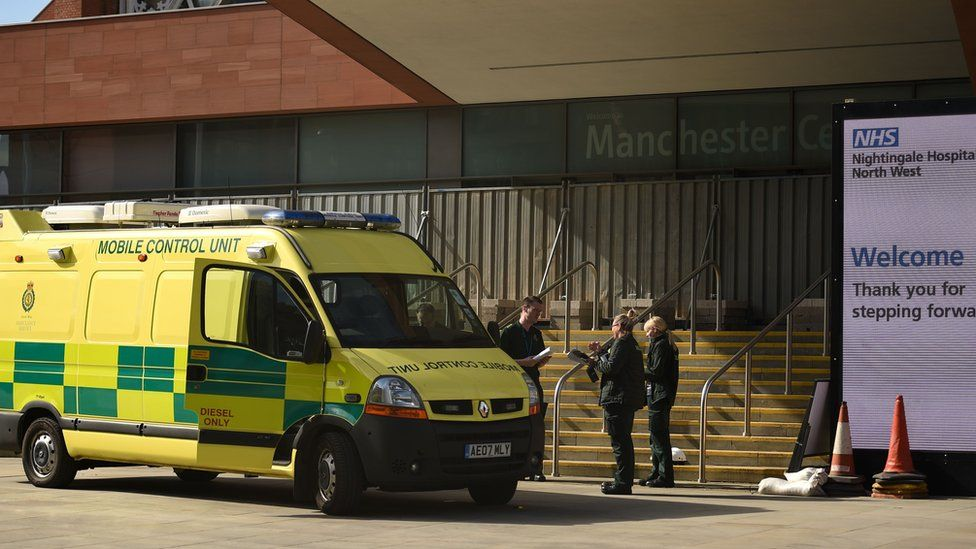 """North West Ambulance Service staff work outside the """"Nightingale Hospital North West"""", the converted Manchester Central Convention Complex, in Manchester, north-west England on April 13, 2020,"""
