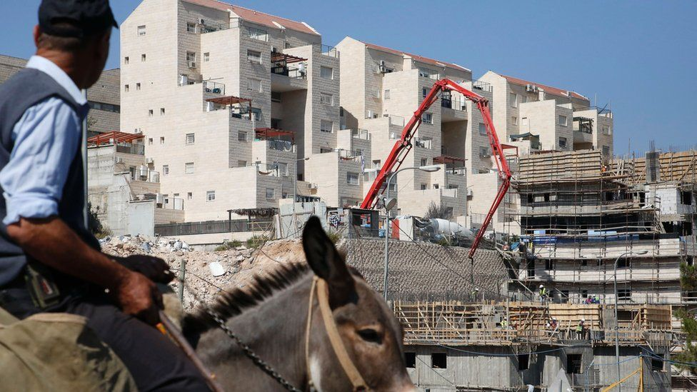 A man rides a donkey past construction workers building new houses in the Israeli settlement of Kiryat Arba, east the West Bank town of Hebron, August 24, 2017