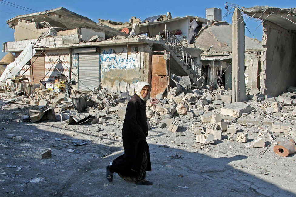A Syrian woman walks past buildings destroyed in a reported government air strike in the town of Maasaran in Idlib province, 17 December 2019