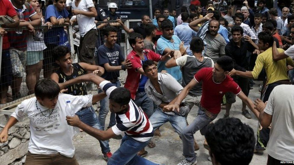 Pakistani, Iranian and Afghan migrants scuffle outside the police station on Kos 15/08/2015