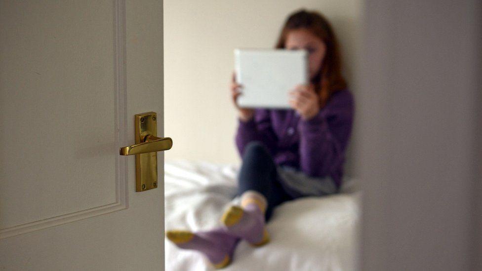 girl in bedroom on tablet