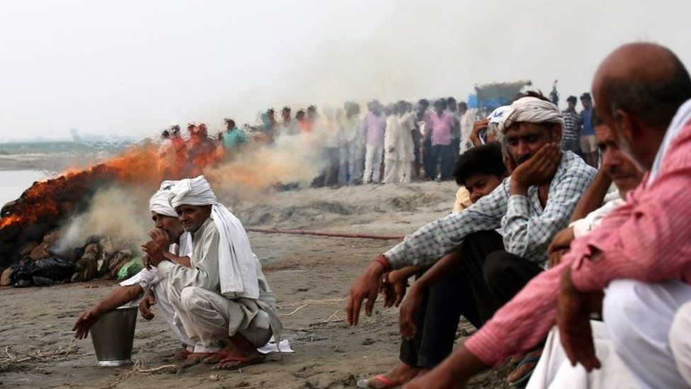 People cremate the bodies of the victims near the site where a riverboat capsized carrying 60 people in Baghpat, Uttar Pradesh, India, 14 September 2017.