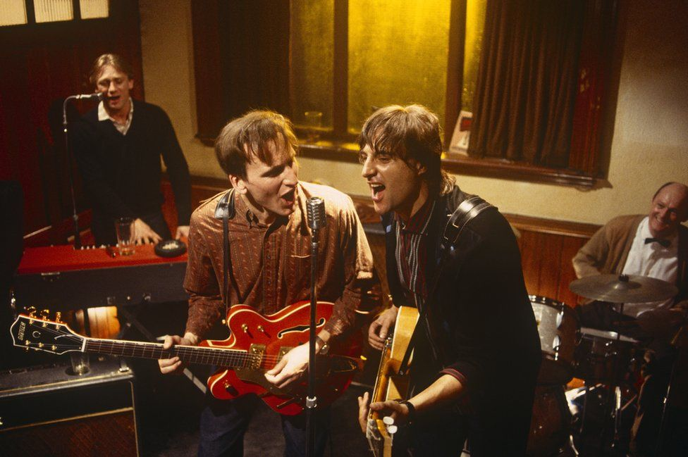Christopher Eccleston (left) and Mark Strong (right) playing guitars in episode one