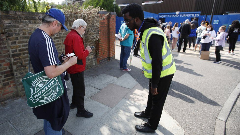 Fans show their Covid status to stewards outside the Women's Super League game between Chelsea and Everton on Sunday