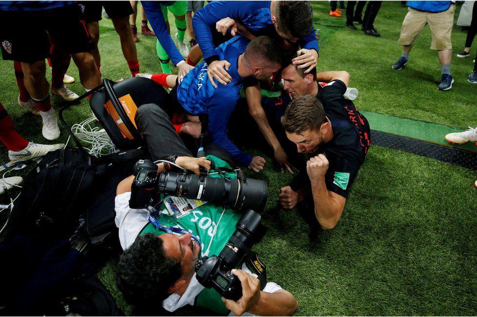 Croatia players celebrate next to an AFP photographer Yuri Cortez after Mario Mandzukic scores their second goal