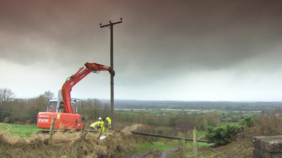 NIE Networks staff work to repair a electricity pole on a country road