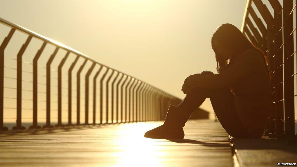 A girl sitting alone on a bridge