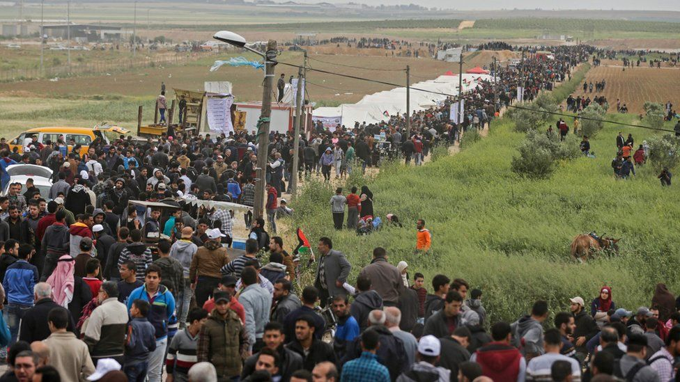 Palestinians march past a tent city erected along the border with Israel east of Gaza City. 30 March 2018