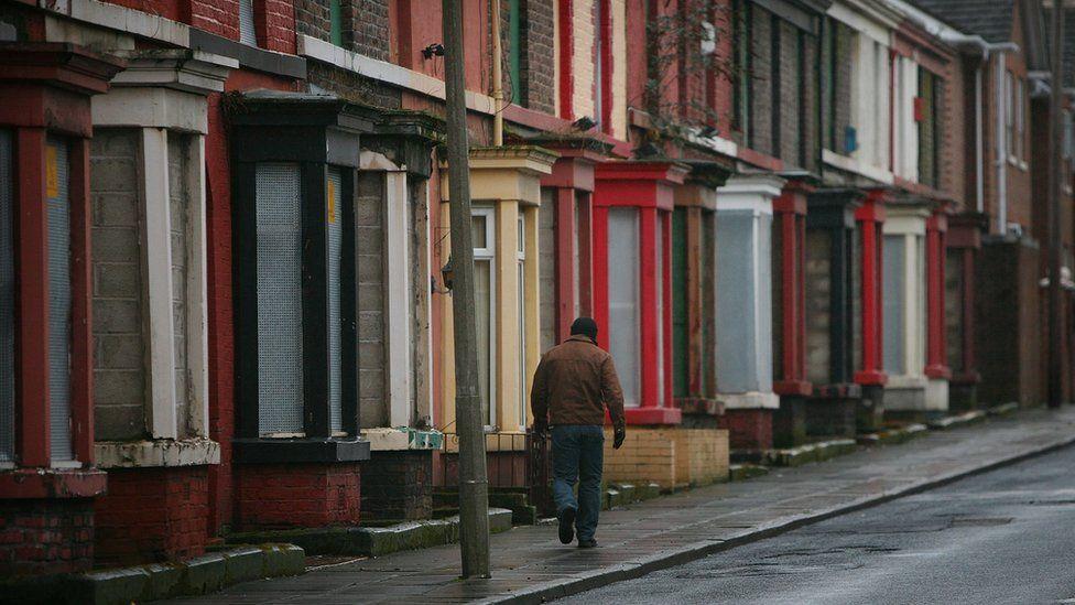 Man walking beside derelict homes