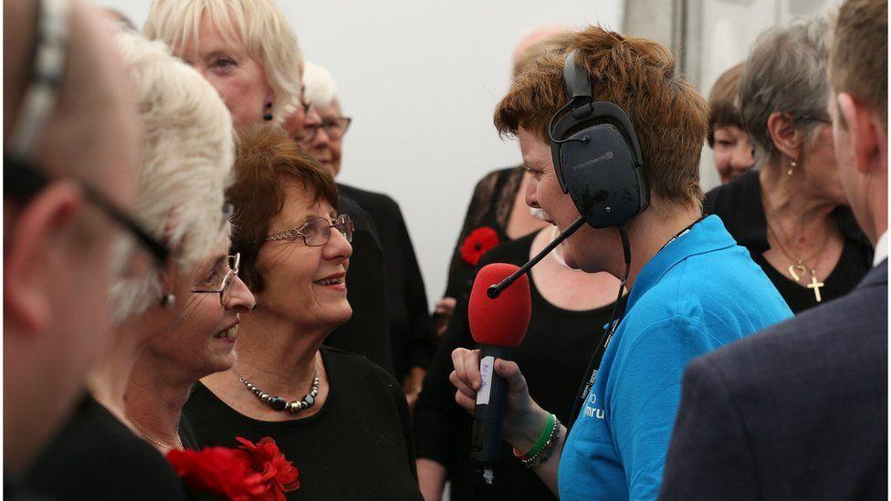 Nia Lloyd Jones yn siarad gyda chôr Henffych ar ôl cystadlu yn y gystadleuaeth Côr Pensiynwyr dros 60 oed. // Members of the Henffych choir being interviewed back stage by BBC Radio Cymru
