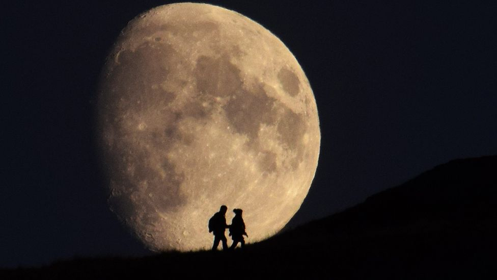 Couple silhouetted by the moon