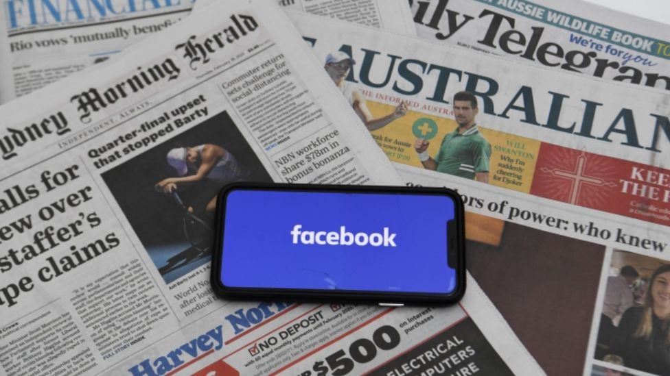A phone showing the Facebook logo on a spread of Australian newspapers