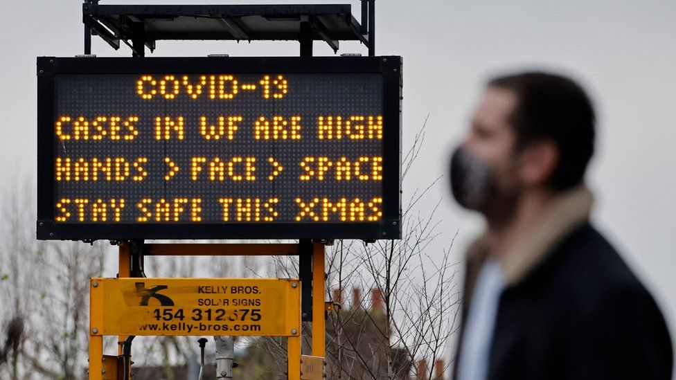 A man walks past a sign warning of high Covid cases
