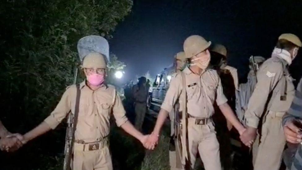 Policemen form a human chain