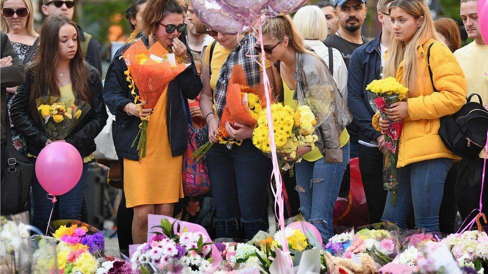 Members of the public pause to look at floral tributes and messages in St Anns Square