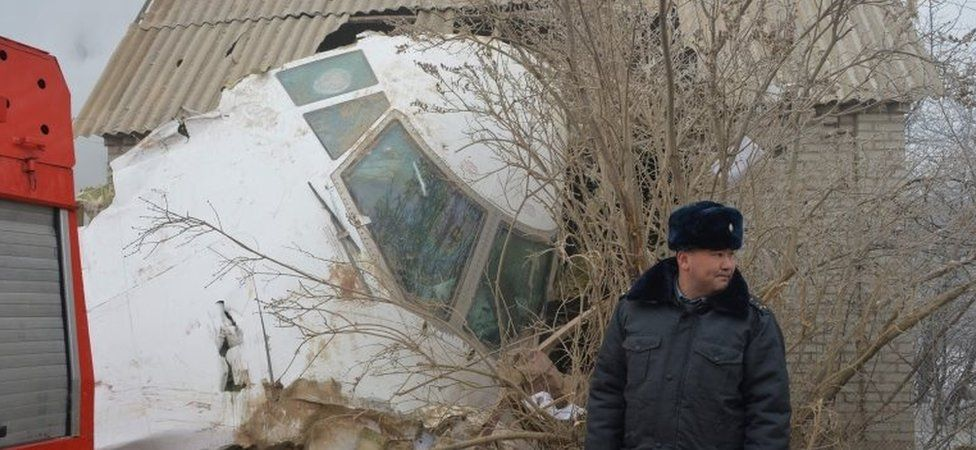 A policeman in front of a Boeing 747 which landed on houses outside Bishkek, Kyrgyzstan (16 Jan 2016)