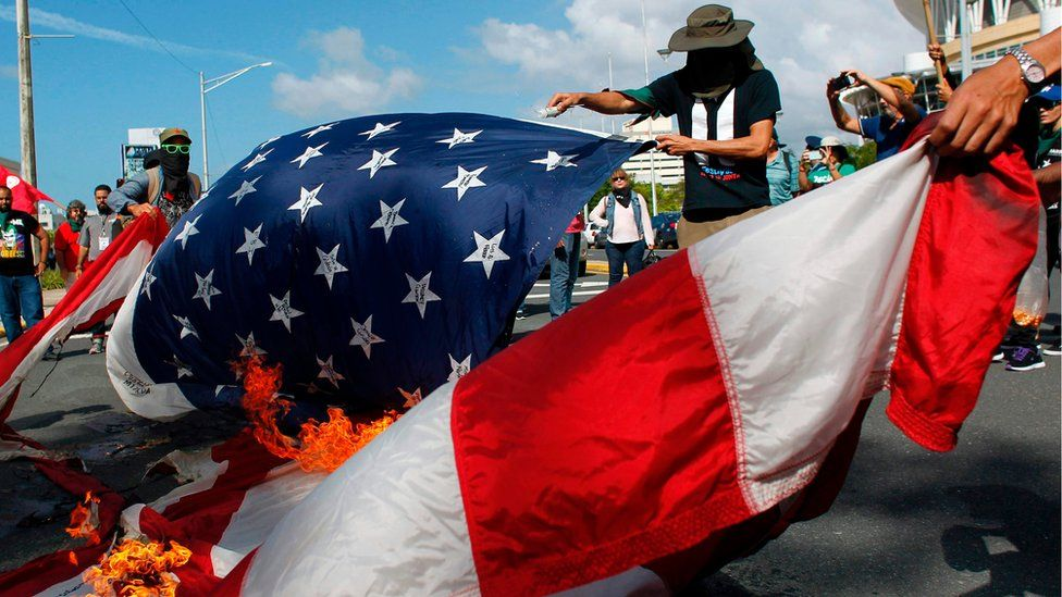 Protesters burn a U.S. flag during a protest against the referendum for Puerto Rico political status in San Juan, on June 11, 2017