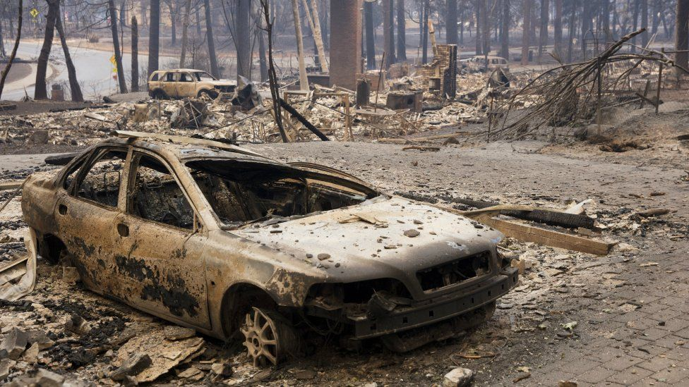 A burned out vehicle sits in the driveway of a Paradise home in Butte County, California, 11 November 2018