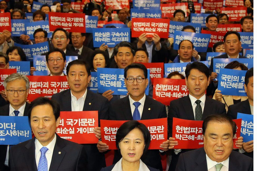 Dozens of politicians from the main opposition Democratic Party, including its chief Choo Mi-ae (centre, front row), hold up signs protesting against the president on 1 November 2016.