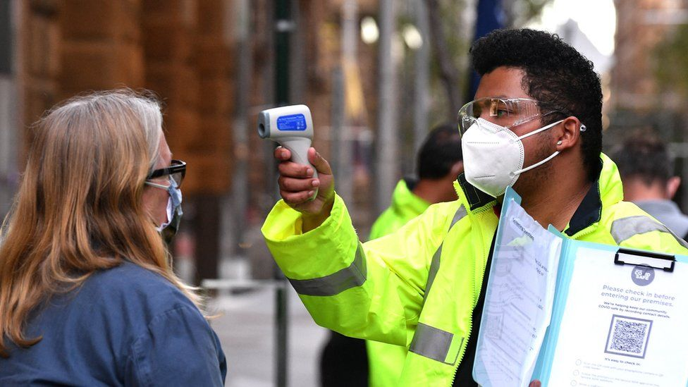 A health worker scans the temperature of someone waiting to enter a medical clinic in Sydney