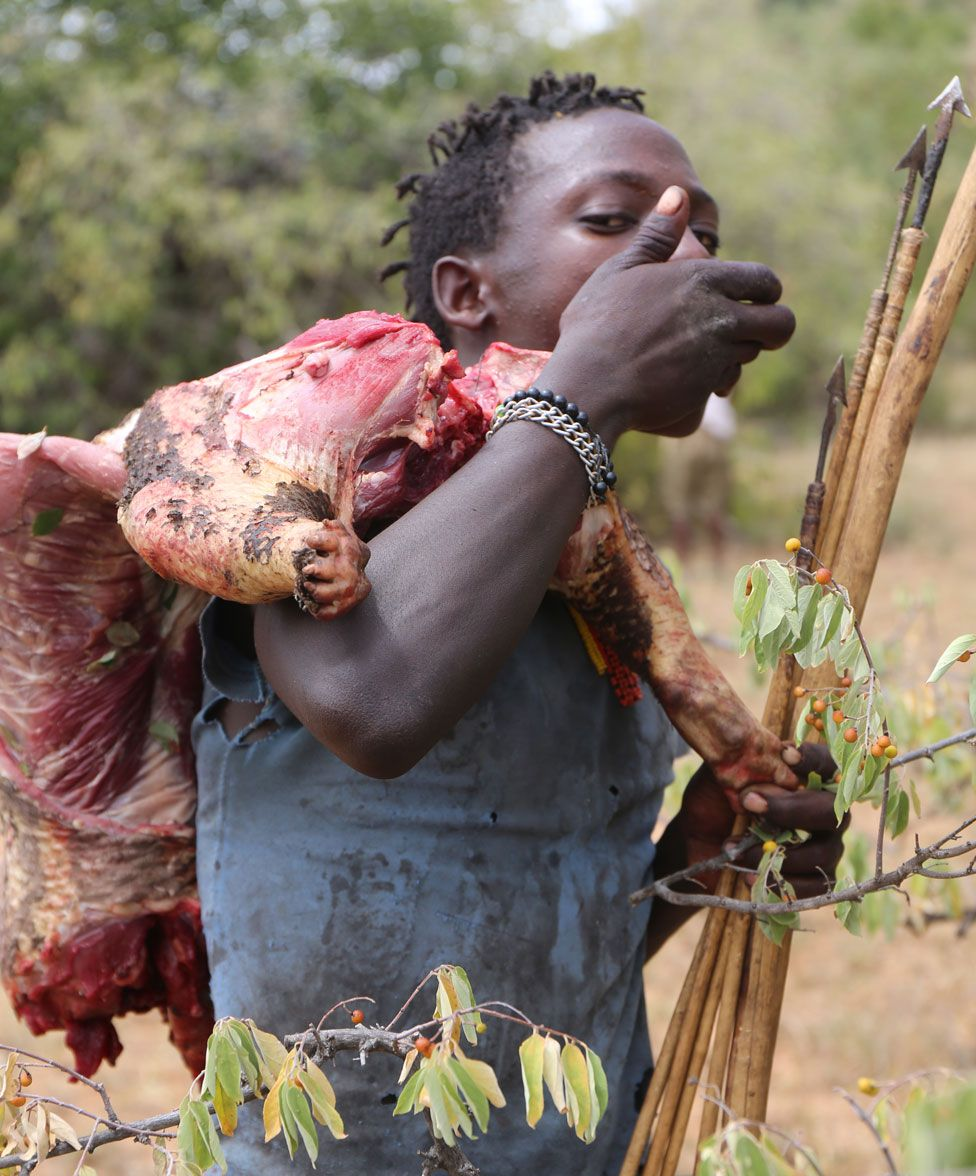 Homem hadza com arco, flecha e um pedaço de carne