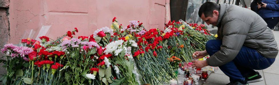 A man lays flowers outside Tekhnologichesky Institute metro station to pay tribute to the victims of an explosion in the metro station