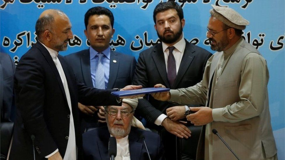 Mohammad Amin Karim (R), representative of Gulbuddin Hekmatyar, and Afghanistan national security adviser Mohammad Hanif Atmar (L) hold a document after signing a peace deal in Kabul, Afghanistan, September 22, 2016.