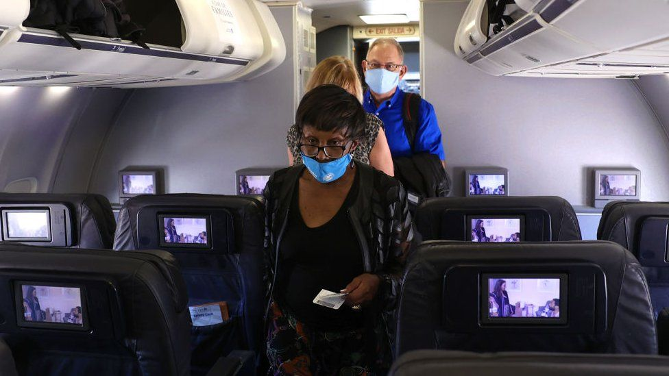 passengers in masks board a United flight