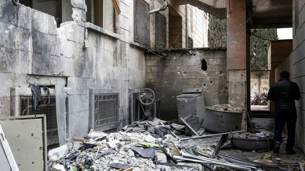 A man inspects damage to a psychiatric hospital in Azaz, Syria, that was hit by mortar fire (19 January 2018)