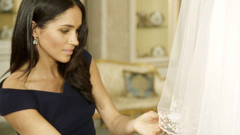 Duchess of Sussex examines the embroidery on her wedding dress