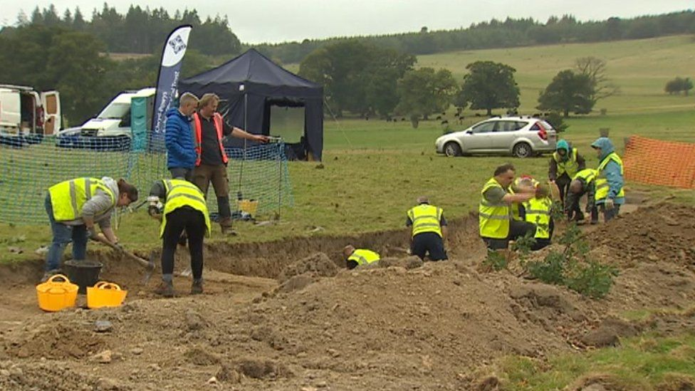 Dig site workers in high-viz jackets start excavations