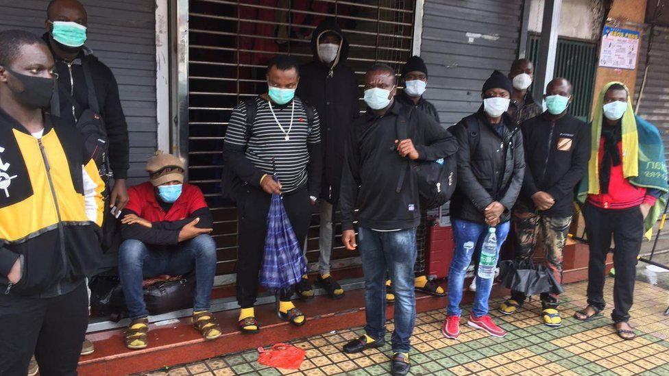 People standing outside a shop with face masks