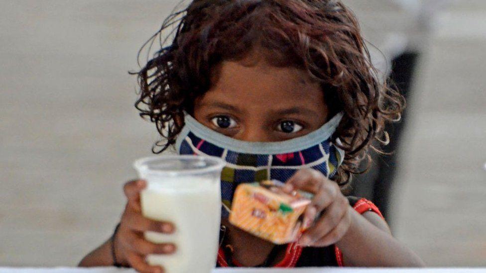Бедный ребенок берет стакан молока и пачку печенья во время бесплатной раздачи стакана молока и пачки печенья, организованной полицией Калькутты на фоне чрезвычайной ситуации с коронавирусом в Калькутте, Индия, 23 мая 2021 года.