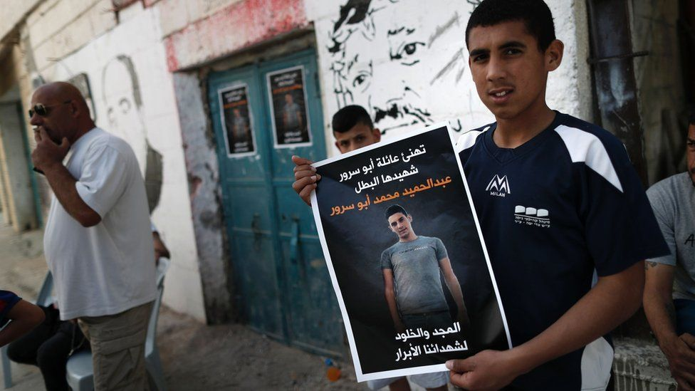 "Palestinian holds up poster describing Abdul Hamid Abu Srour as a ""martyr"" at the Aida refugee camp"