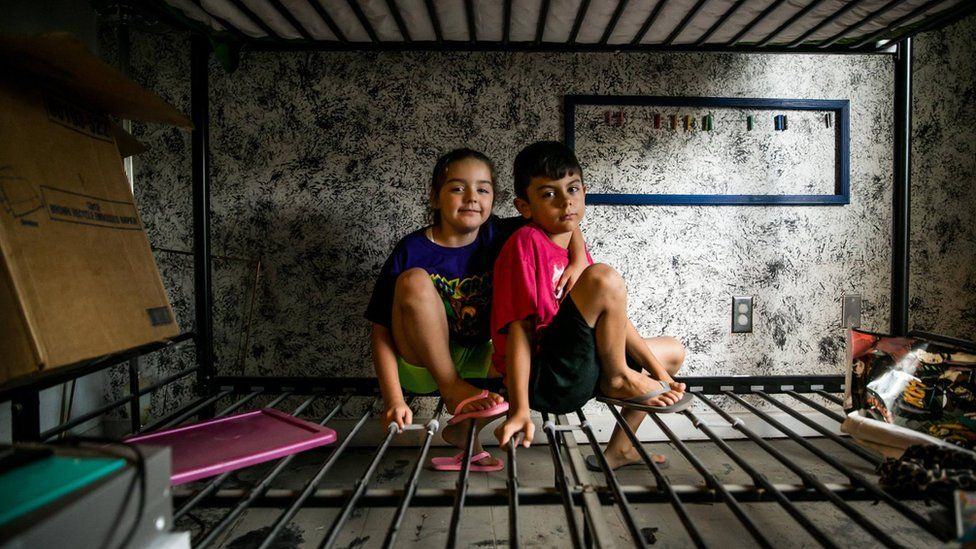 """Aiden and his little sister, Jubilee, sit on what's left of their bunk beds in the Baton Rouge home that was new to them just months ago. Their mother, Mimi, said: """"Today we're going to call it an early day so that Aiden can celebrate his birthday, because not even this flood should get in the way of that."""""""