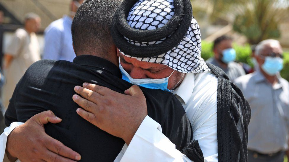 Mourners hug each other at the funeral of Hisham al-Hashimi in Baghdad (7 July 2020)