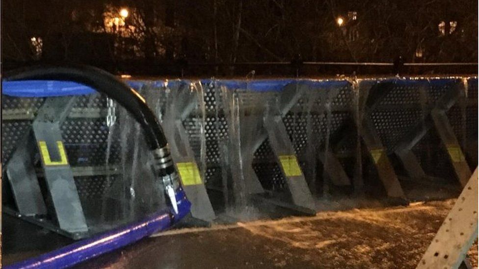 Water pouring over flood barriers in Bewdley, Worcestershire