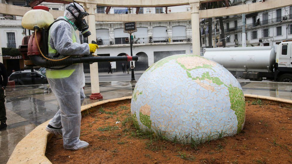 A worker wearing a protective suit disinfects a globe-shaped public garden in Algiers, Algeria - Monday 23 March 2020