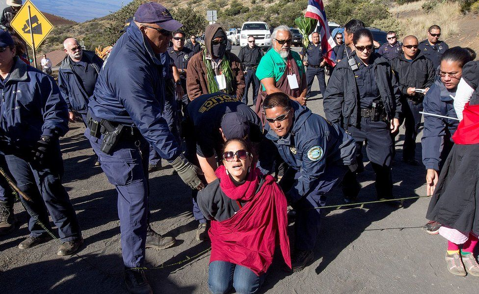 In this April 2, 2015, file photo, Department of Land and Natural Resources officers arrest a Thirty Meter Telescope protester at the telescope building site on the summit of Mauna Kea in Hilo, Hawaii