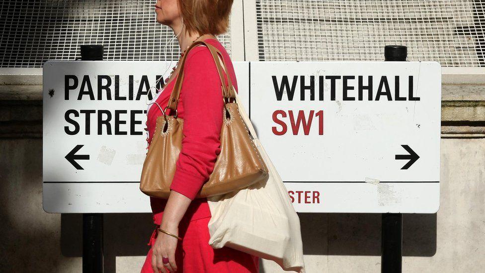 Woman walking Whitehall sign