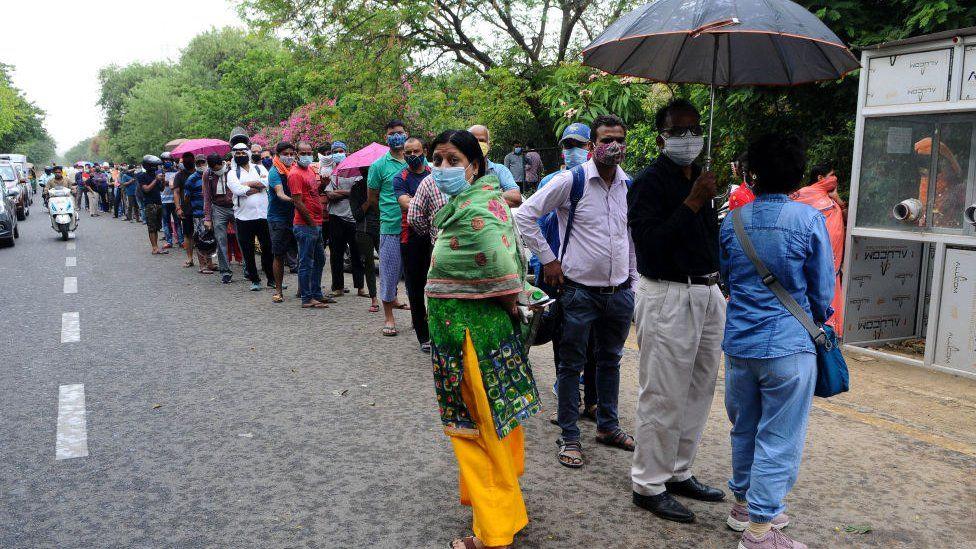 Люди ждут своей очереди на тестирование COVID-19 в испытательном центре в Газиабаде, Уттар-Прадеш, Индия, 23 апреля 2021 года.