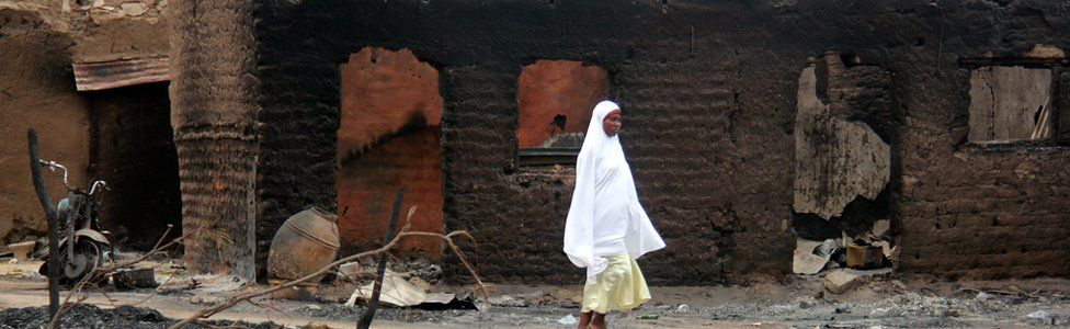 a woman walks past burnt houses in Baga After clashes involving Boko Haram fighers - 2013