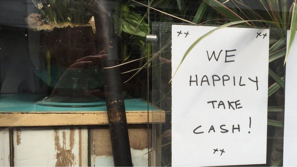 Sign saying shop accepts cash