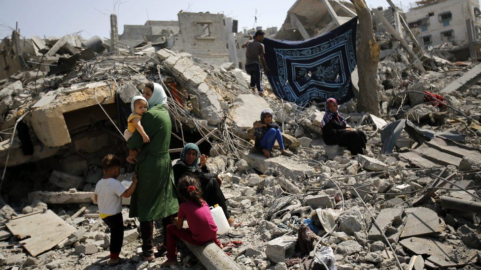 A family inspects the remains of their destroyed home in Beit Hanoun, in the northern Gaza Strip (1 August 2014)