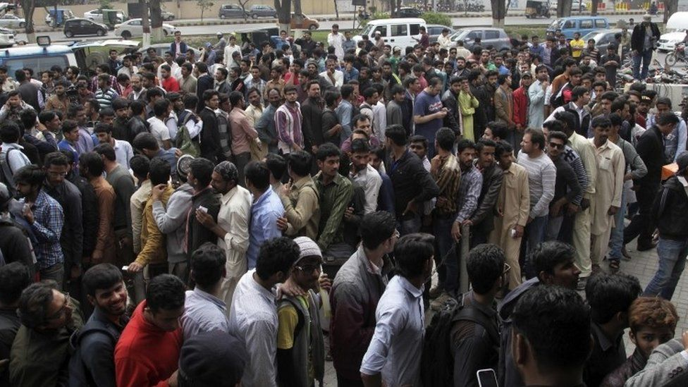 Cricket lovers gather outside a bank to buy tickets for the upcoming final cricket match of the Pakistan Super League, in Lahore (01 March 2017)