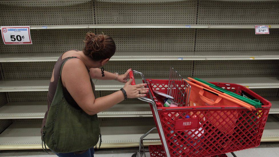A woman looks at empty shelves that are normally filled with bottles of water in a supermarket in San Juan, in Puerto Rico