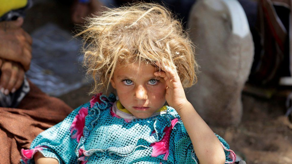 Displaced Yazidi fleeing Islamic State militants in Sinjar rests at the Iraqi-Syrian border (13 August 2014)