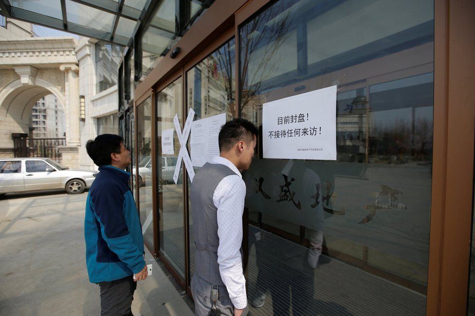 """People look through the windows of a sales office of a property, with a paper on the window reading """"The property is currently closed; do not accept any visit"""", as the government banned new property sales in counties earmarked as part of a new special economic zone in Xiongxian, Hebei province, China, 3 April 2017."""